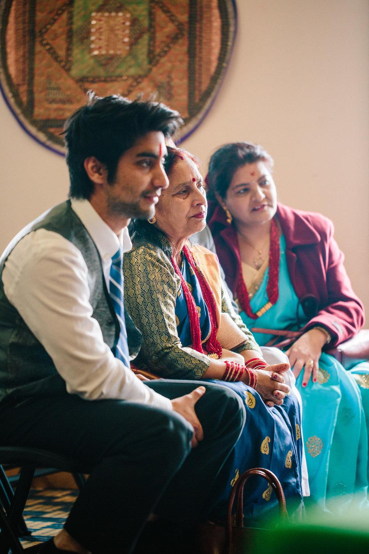 Nepali mother of groom watches Hindu wedding ceremony in temple Madrid Iowa photographers