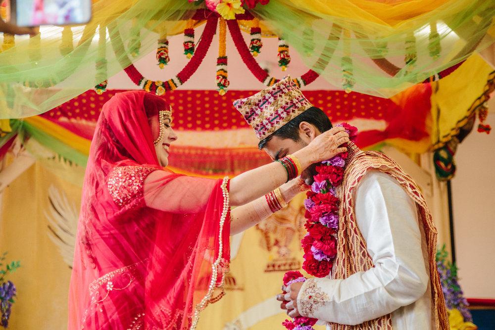bride and groom exchange flower garlands during wedding ceremony