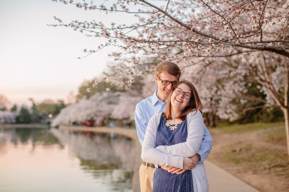 guy and girl hugging under blooming cherry tree Washington DC tidal blossoms