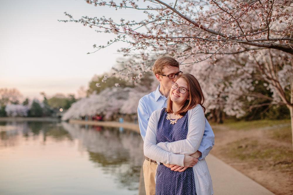 guy and girl hugging under blooming cherry tree Washington DC tidal