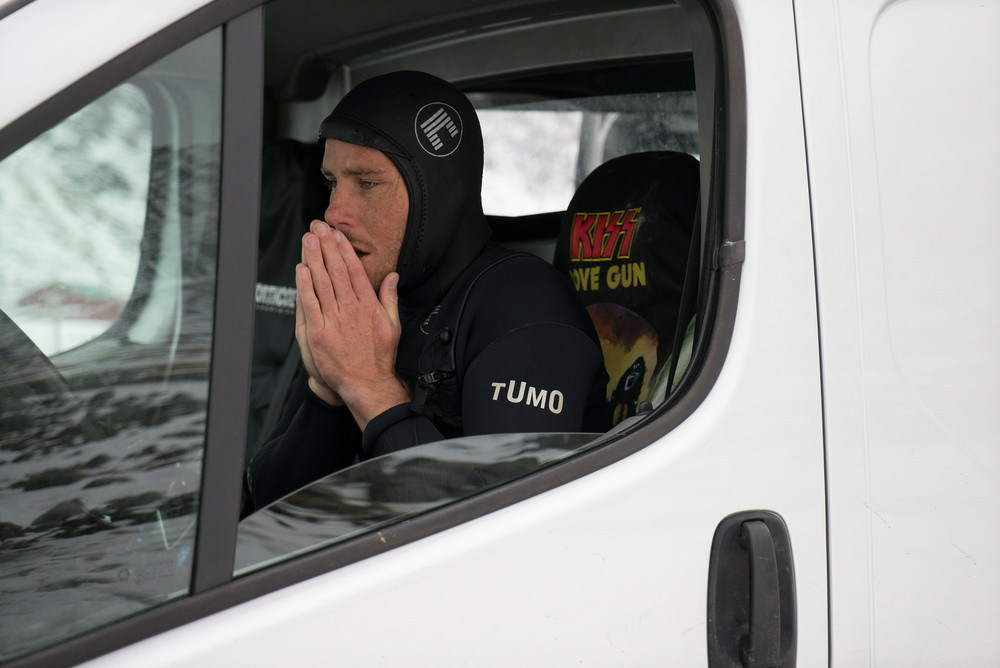 Pat warms up his hands in his KISS van after a morning session in the frigid Arctic waters.