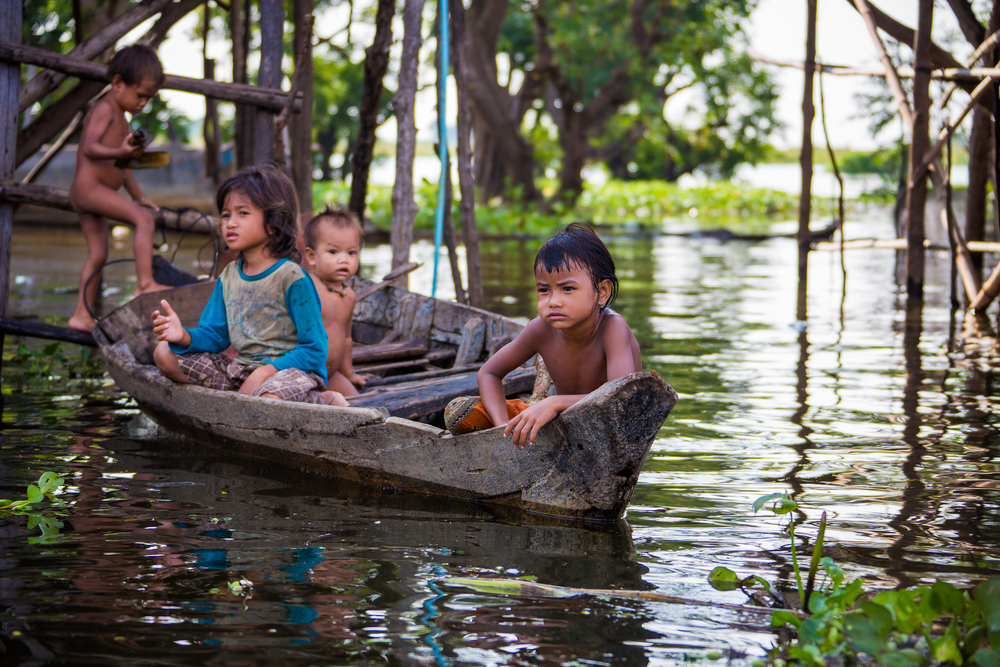 A group of children sit on their boat outside of their home in a floating village on the Tonle Sap River in Cambodia.