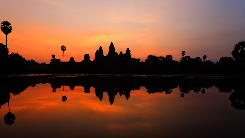 The sacred temple of Angor Wat lights up in front of an early morning Cambodian sunrise.