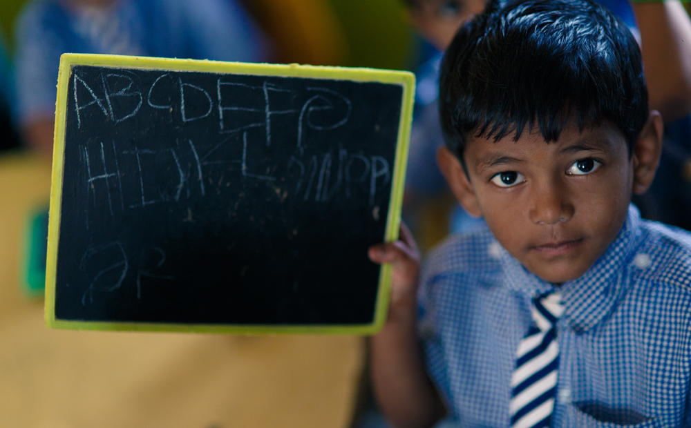 A boy shows he can write his ABC's at a school in India.