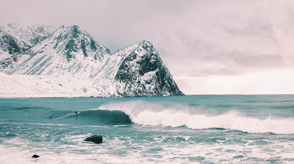 Waves break in front of the snow capped peaks of the arctic circle.