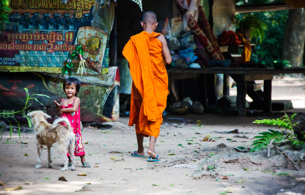 A Monk walks through the Tep Preah nom Pagoda while a girl and a dog play in the humid mid morning Cambodian air. Canon 5D Mark III, Canon 28-300, 1/500 sec, f/5.6