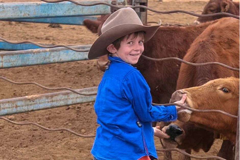 Young Oscar with a couple of orphaned poddy calves on Canaway Downs in south west Queensland. Photo: ABC, Jody Tully.