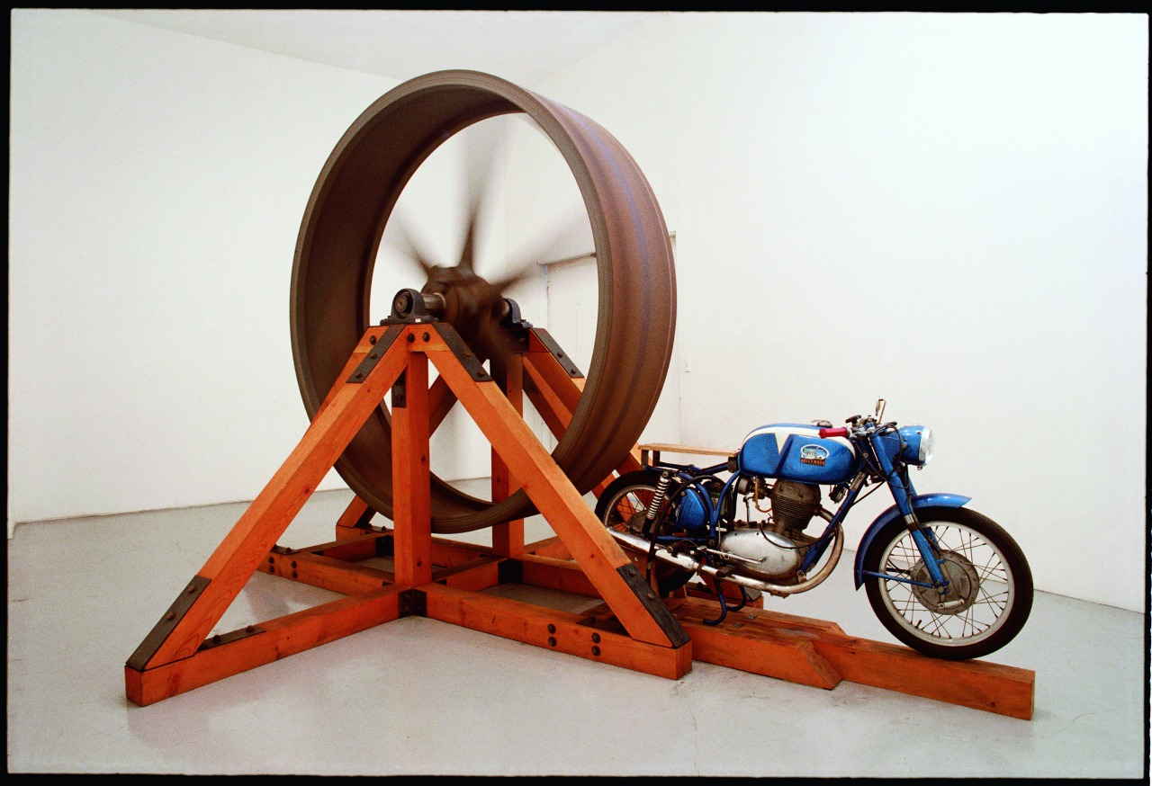 "newmuseum: New details announced for ""Chris Burden: Extreme Measures"" from our Press Office here. Pictured here is The Big Wheel (1979) which presents a 6,000 lb cast-iron fly wheel that is activated by a motorcycle. When the motorcycle is accelerated at full throttle, the fly wheel spins to a maximum speed of 200 RPM.  Image: Chris Burden, The Big Wheel, 1979. Three-ton, eight-foot diameter, cast-iron flywheel powered by a 1968 Benelli 250cc motorcycle, 112 x 175 x 143 in (284.5 x 444.5 x 363.2 cm). The Museum of Contemporary Art Collection, Los Angeles"