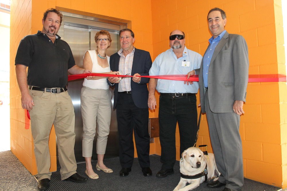 Local community member Sam Coward, C-Square owner Tracy Martin, Cr Greg Rogerson, patron Peter Ryan with Pebbles the dog, and C-Square owner John Sorrentino launching the lift in May 2014