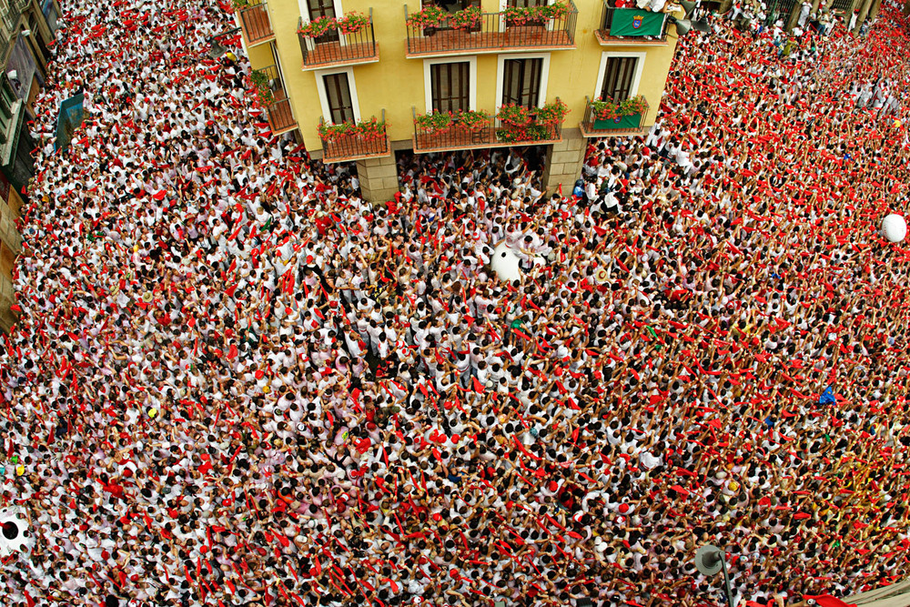 I shot Pamplona's iconic running of the bulls for an article I wrote for Explore magazine in 2005. Proper research and networking were vital in order to get a spot on a balcony where the start of the fiesta takes place. Luckily, through a friend of a friend, I was able to secure a spot overlooking the main square. That was more than half the battle. But to get far enough out to exclude the awnings below me, I had to lean over a lot farther that I would have, had a friend not been holding on to me! Officials say the square reaches maximum density when there are five people per square meter. Looking at this image, that seems about right. Canon 20D, Canon 15mm fisheye. ISO 200, 1/350 at f/6.7. Photo and story by Mike Randolph, randolphimages.com.