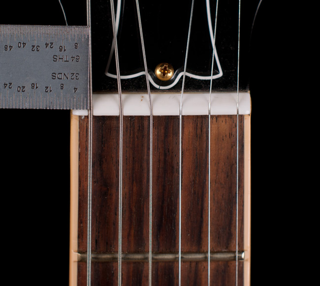 "The low E string on this guitar is 5/32"" from the edge of the fingerboard which is good considering the binding covers the ends of the frets.  However the high e is too close to the edge of the fingerboard ( see next photo )."