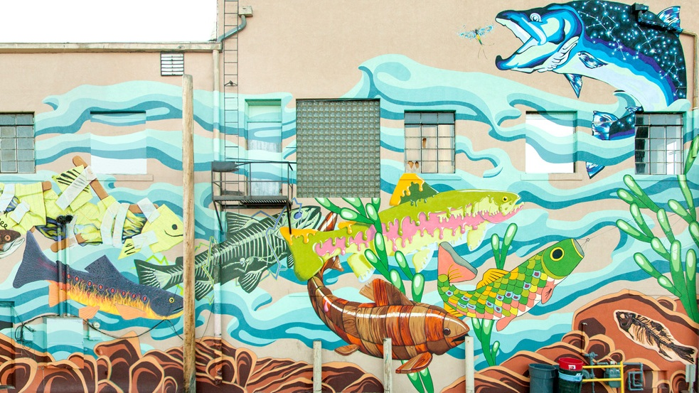 Gill Street , the collaborative fish mural can be seen from the parking lot behind Coal Creek Coffee and Alititude's Chophouse at First and Grand and First and Garfield, or from the historic Garfield Street Footbridge. It was dedicated on June 13, 2014. Artist Include: Colleen Friday, Jeff Hubbell, Travis Ivey, Evan Levi, Chelsea Lowry, Meghan Meier, Lindsay Olson, Dan Toro, Adrienne Vetter.