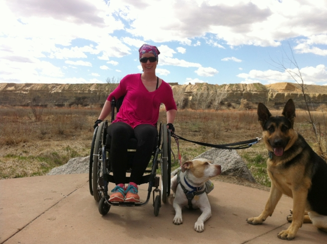 Nerissa, the author of this article, walking 2 dogs from her everyday wheelchair using standard leashes.