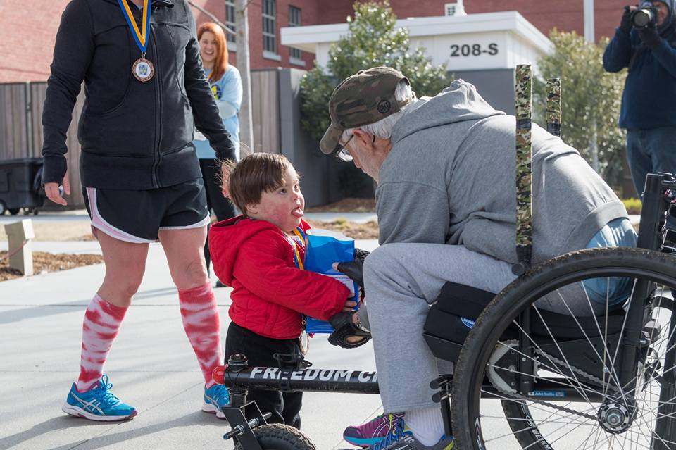 """Me being awarded my 1st in age group . . . last Saturday. The race was a fundraiser for a local Down Syndrome support group . . . It was my best time yet and being presented the award by such a cute little guy was icing on the cake.""  -  John Hollis"