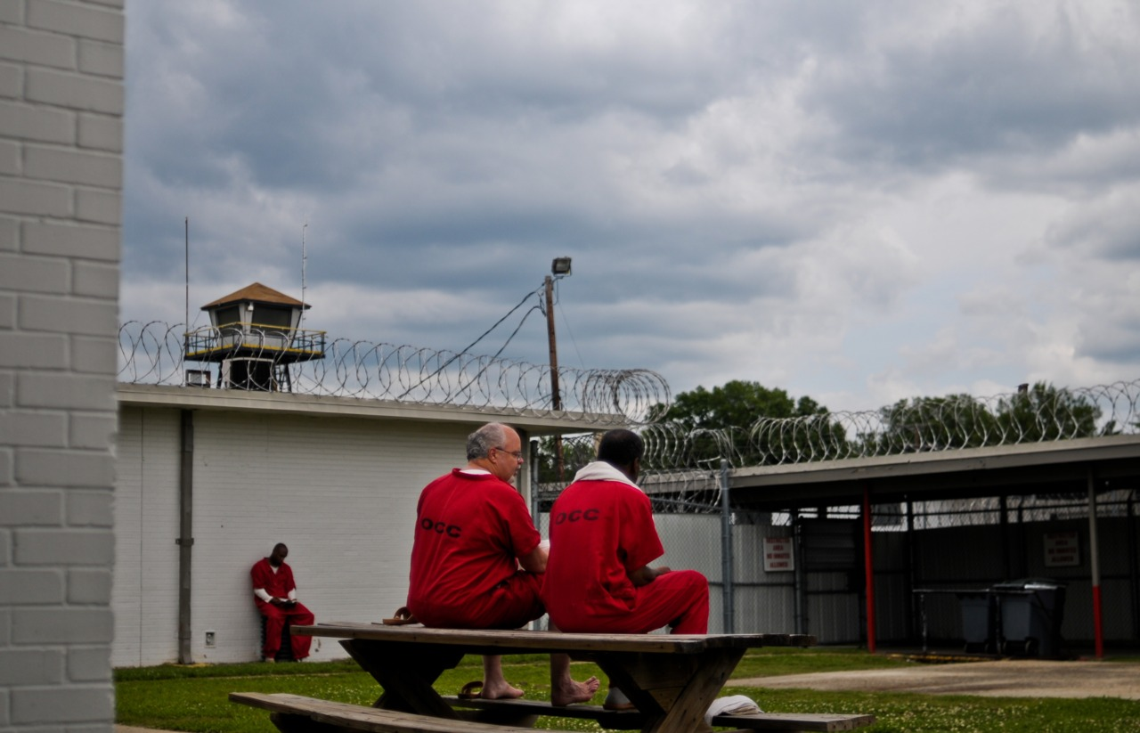 Two offenders sit in one of the yards at Ouachita Correctional Center.