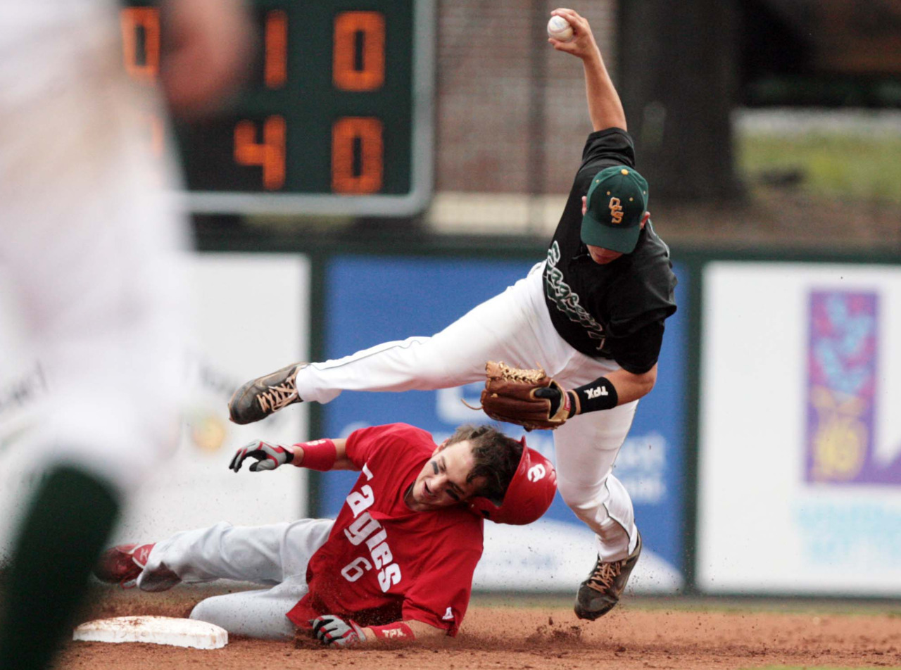 OCS' Jordan Washam (7) tries to tag out Central Catholic's Luke Landry (6) as he slides to second base during the LHSAA 1A State Championship game on Saturday in Ruston against Central Catholic. OCS won the game 10-0.