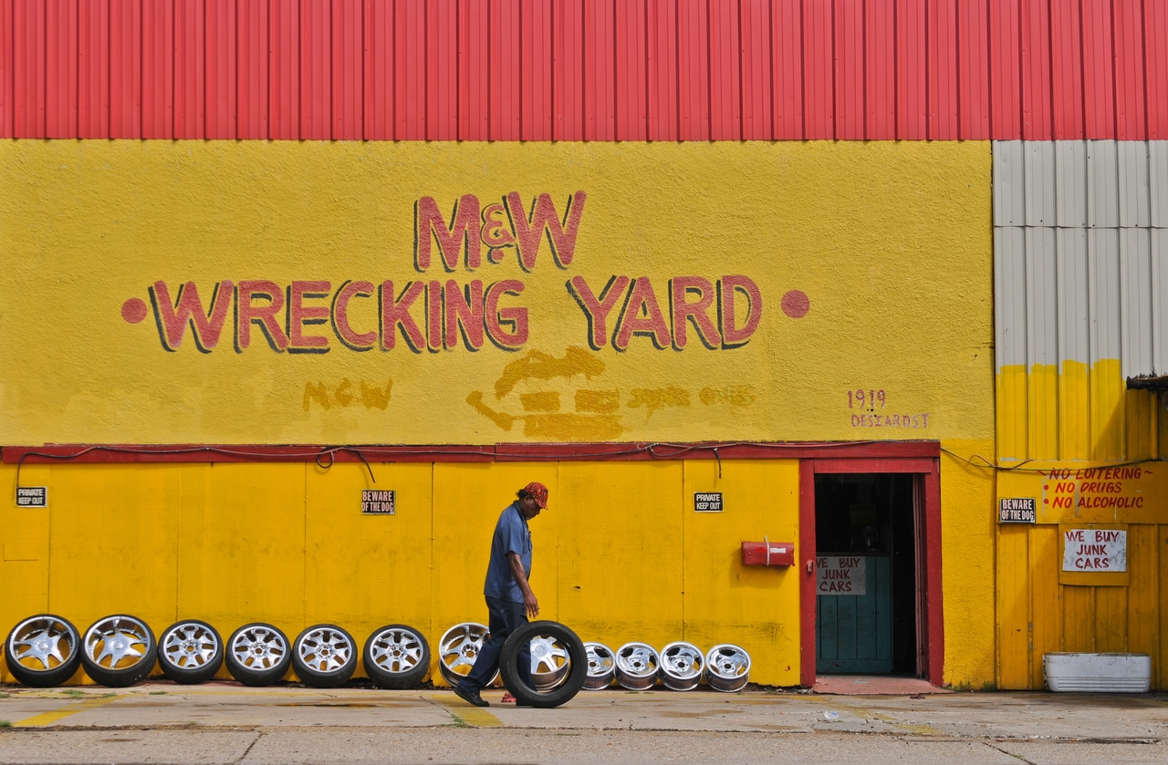 Willie Mitchell owner of M&W Wrecking Yard on Desiard Street rolls a tire to a customer's car.