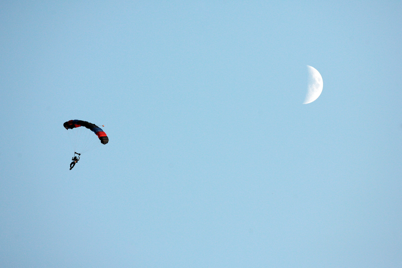 A parachutist drifts past the moon before the ULM vs. Baylor football game in Monroe, LA.