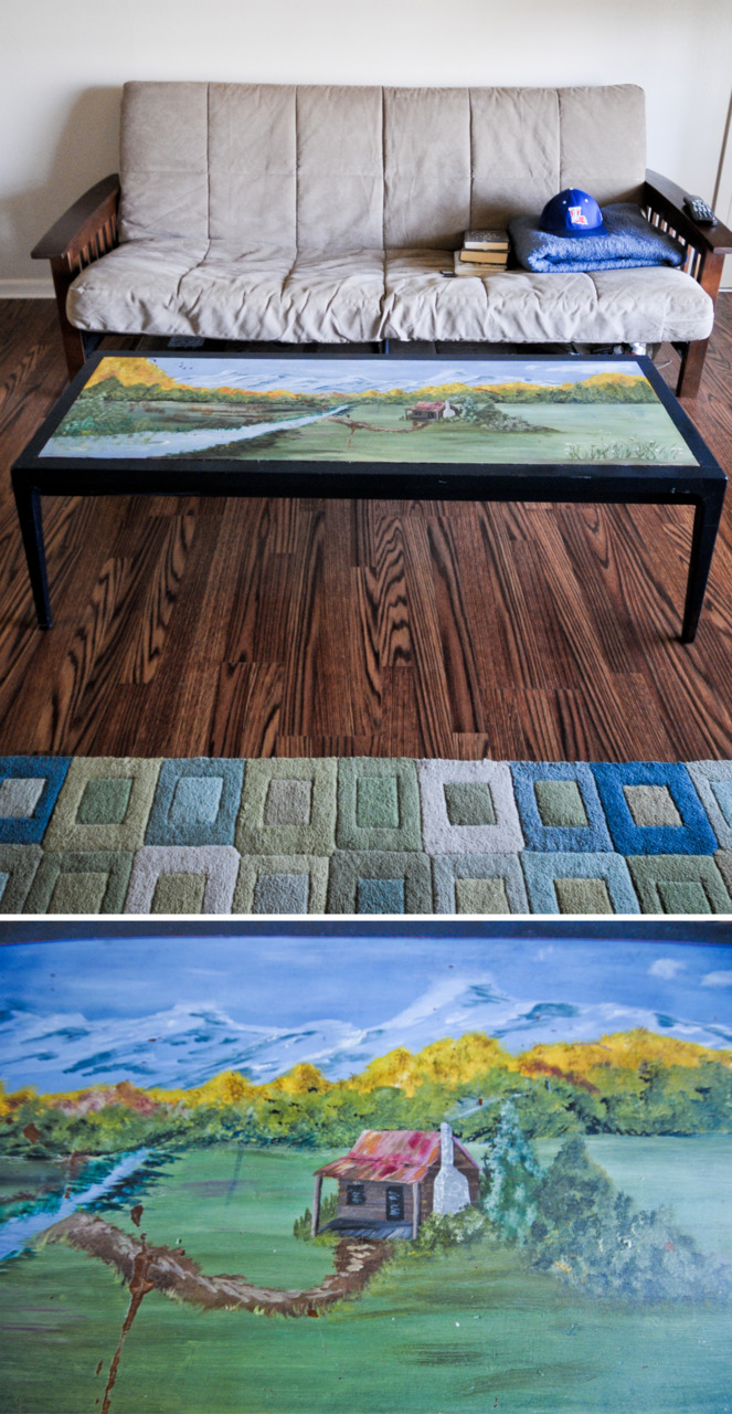 "The Awesome Table:   I walked into Goodwill and spotted it immediately. It was hard to miss. A blue coffee table with a landscape painted on it. Since I don't currently have a coffee table, I have been using a cool spray painted foot locker. Don't judge. Therefore I wanted this table. I walked around the store just to make sure that I couldn't live without it. I brought it proudly to the check-out and the cashier gave me a strange look. ""You must be single,"" she said. I nodded my head, a bit thrown off by the statement, and she proceeds to tell me that no married woman would have that in her house. So many things I could have said back, but I just laughed and said it would match everything in my place, receiving a horrified look. She mumbled something about man caves and ten bucks later I was trying to fit it into my car.    When I got home, I cleaned it and sprayed it with a coat of clear Krylon. I don't know if you have ever read the directions of Krylon, but you should - especially if you live in the South. ""If extremely humid, do NOT use."" Yeah, whatever. I would have to wait a couple months. It came out a little hazy as usual, but I will just give it another coat to clear it up when it a little less humid outside. I also might paint the blue trim a more neutral color.    No more foot locker."