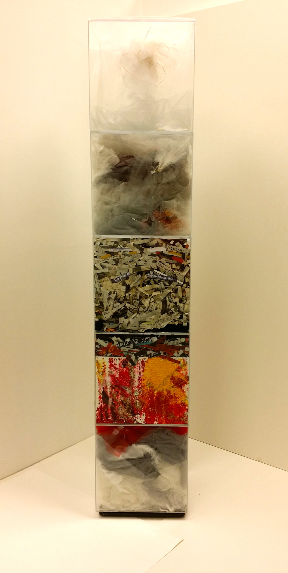 An Hypothesis, 2015  12 x 12 x 62 inches  Five acrylic cubes containing dyed gray gauze, lightweight tulle, feathers, newspaper clippings, textured acrylic drawings, and dripped paint, arranged in the boxes so as to fill and modify their space. Each cube defines a separate space, yet the content of each bleeds into the next, connecting them into the whole. While the contents can be seen as unrelated, they can also be perceived as one in essence. The stacked boxes suggest an orderly sequence, hinting at a logical cycle in which the materials are arranged.