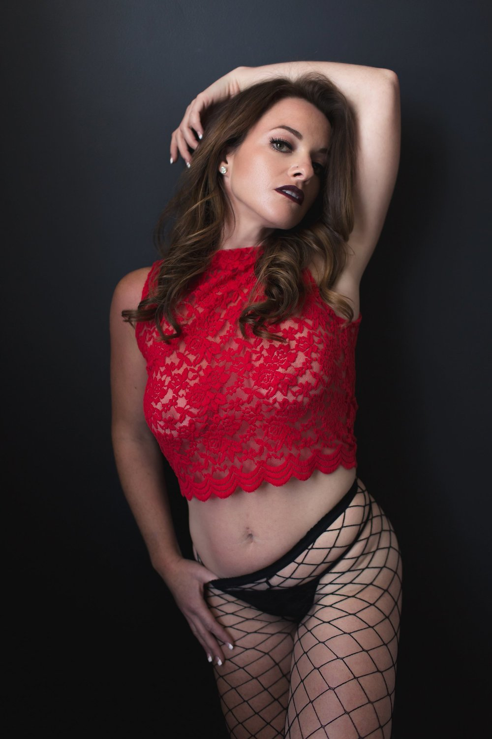 Sensual woman in red lace top and fishnet stockings