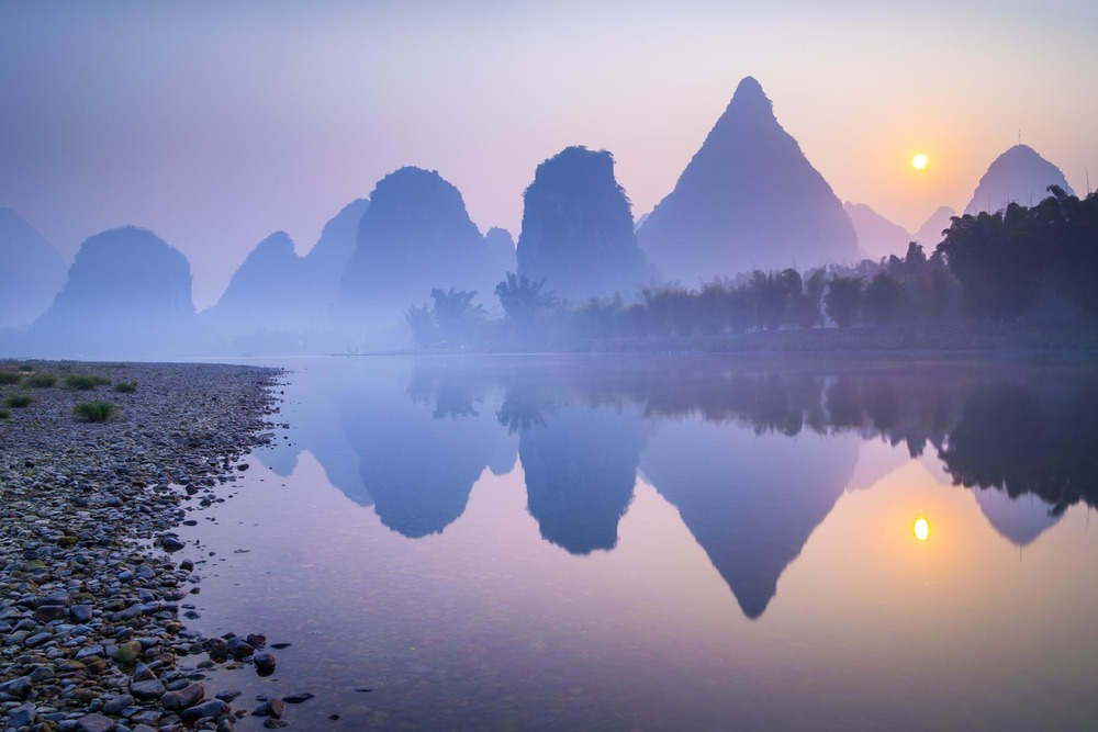 Mountains reflecting over the Li River at sunrise. China