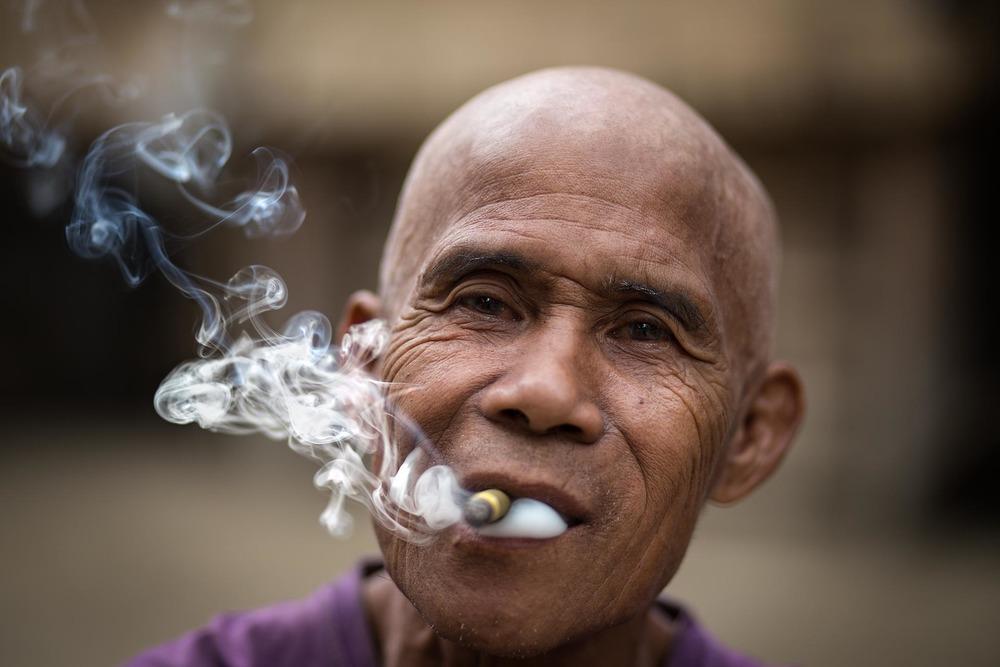 Chin man smoking a cigar in Rakhine state. Myanmar