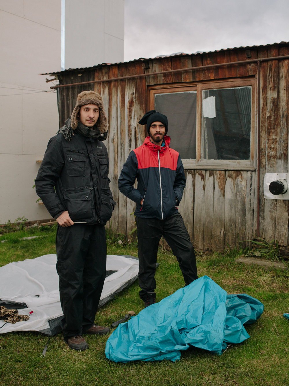 Yuri and Estevan, two backpackers from Brazil setting up their tent in a private garden of a couchsurfer. Due to the very expensive cost for accommodations in Ushuaia, many young travelers decide to use alternative ways of traveling.