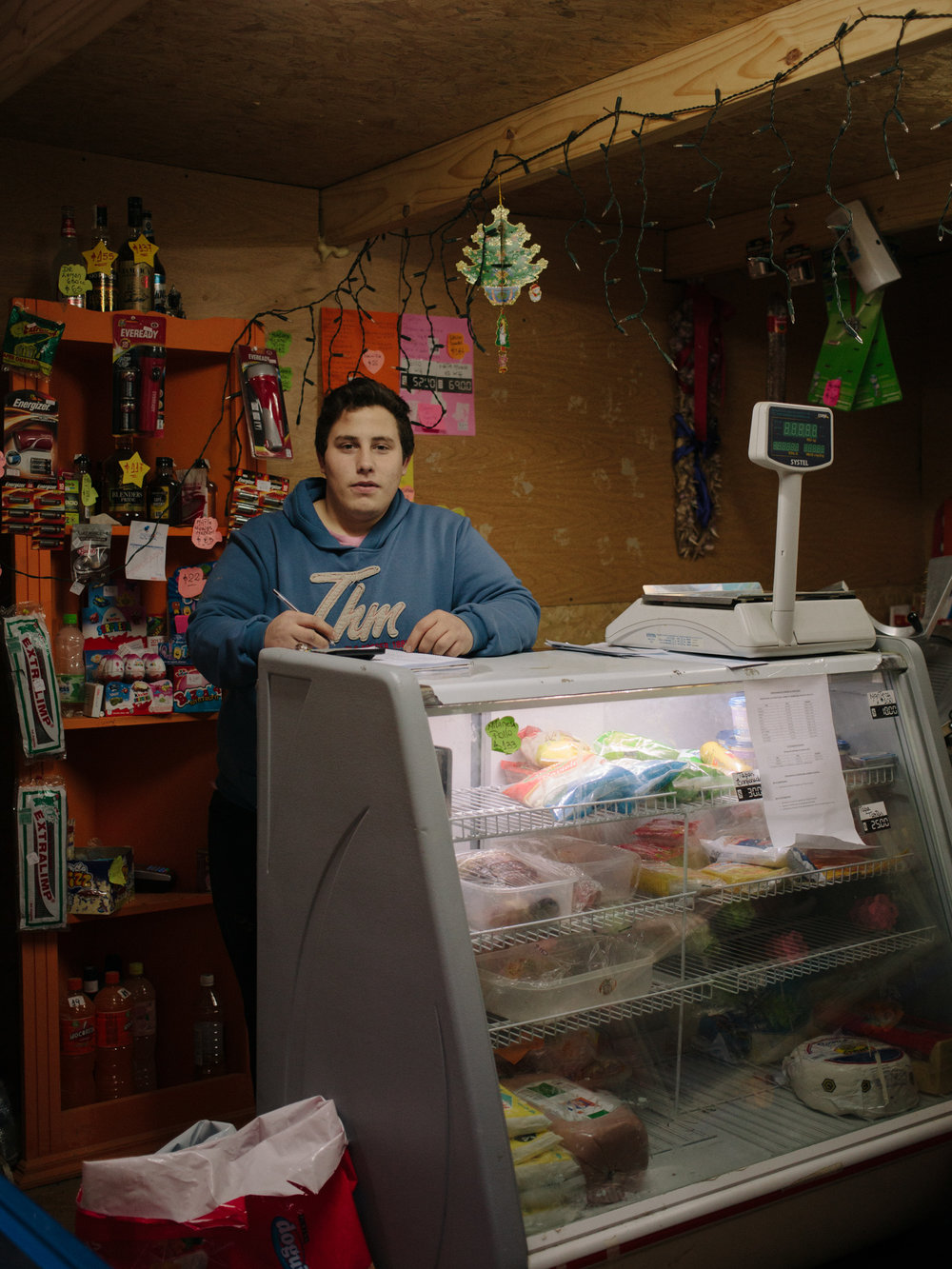 Augustine, works as a clerk in one of the few kiosks inside the occupied district ' Dos Banderas '. In the middle of the woods, his kiosk is probably the best equipped ones and people from all over the district walk here to buy their essential needs.