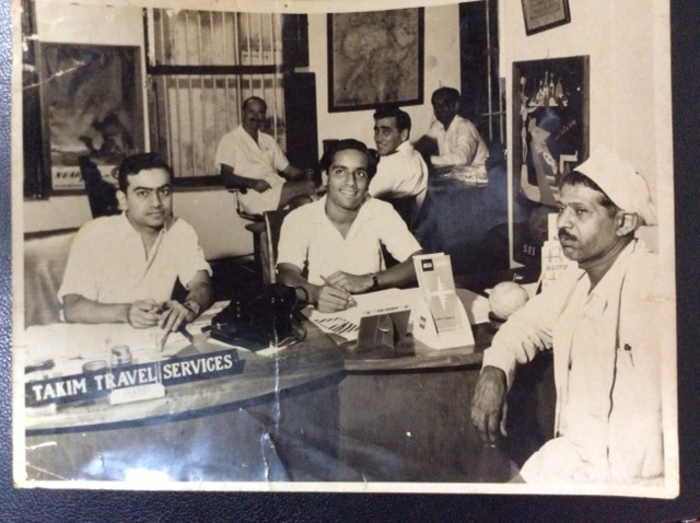 The Takim Travel Service office during its humble beginnings in Zanzibar. In the background are the management team of East African Airways with Akber Takim, the founder of Takims Holidays
