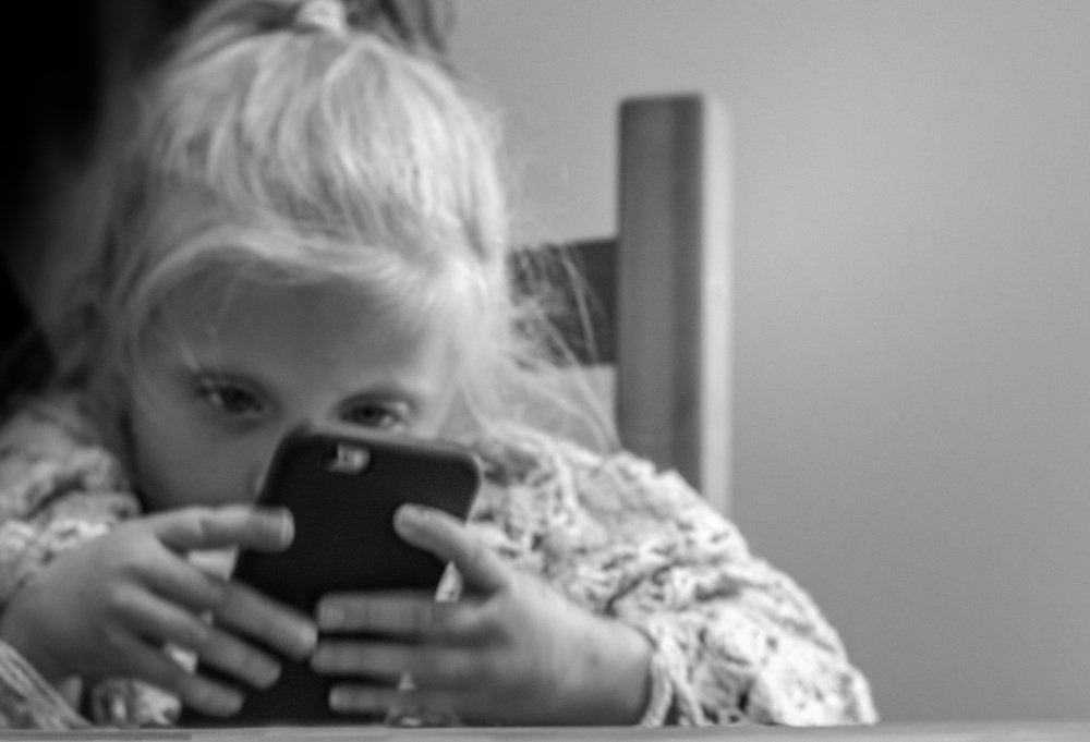 "Still wearing Blanky, Tori plays with her Mom's smartphone.  It is amazing to watch this not quite 3 year old manipulate the games on the phone.  ""Tori and the smartphone"" (c) Rebecca LaChance, 2015, Aurora, CO"