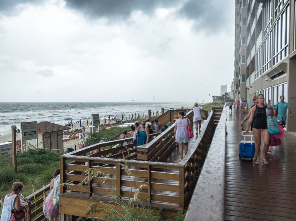 """Beach Exodus"" (c) Rebecca LaChance, 2016, Panama CIty Beach, FL.   We were overly optimistic.  Despite the stars and open skies of the early morning, today was another stormy day with double-red flags on the beach.  Double-red flags mean the surf is filled with rip currents and you are to stay out of the water.  This is the line of people hurrying to leave the beach as the clouds opened with another downpour."