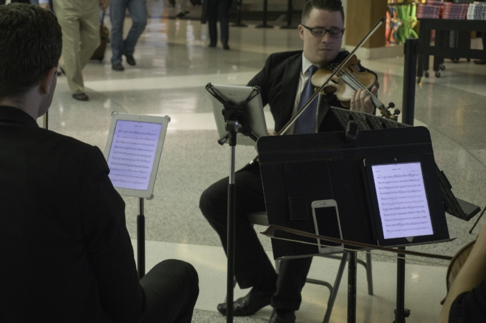 """Classical Technology"" (c) Rebecca LaChance, 2015. Houston Hobby Airport.  There was just something striking about a string quartet (Divisigns) playing ""Shake it off"" in a classical mode with the ""sheet"" music on IPads.  This group was PHENOMENAL.  If they had a CD, I would have bought it on the spot!"