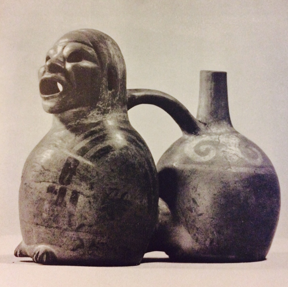 "Double vessel, Mochica. Clay, 6 3/4"". If this vessel is dipped when filled with liquid, it emits a mournful sound, which accounts for the open mouth of the figure."