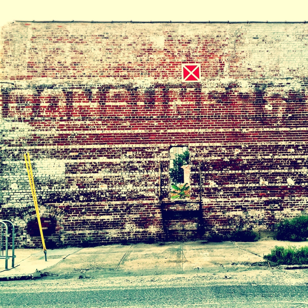 You will be seeing more of this wall in the future.  I am working on a housing development on this site and this old wall will be incorporated into the design.  The ghost sign says 'CONSUMERS', and on the part that I cropped on the right side it says 'ICE CO'.