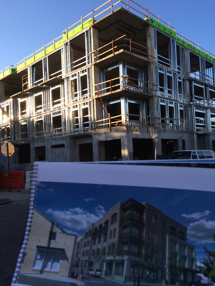 Construction photo of The Spectator with me holding up the rendering in the foreground.