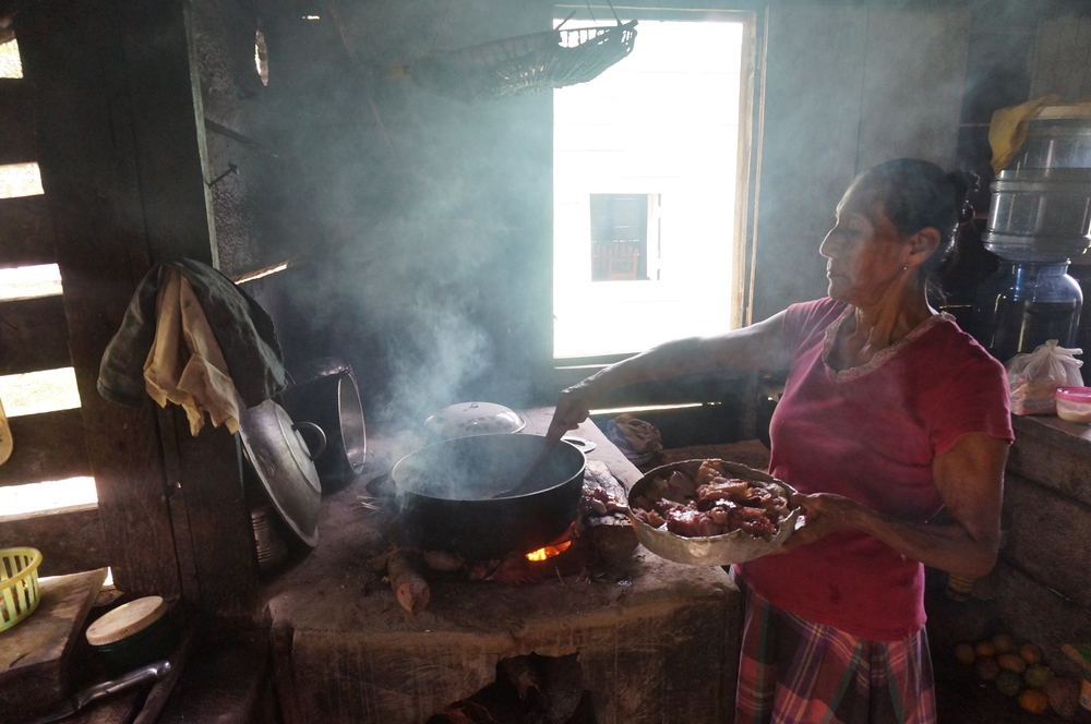 A woman in TikTik Kaanu, Nicaragua cooks over an open flame indoors. - Photo credit: Giana Amador