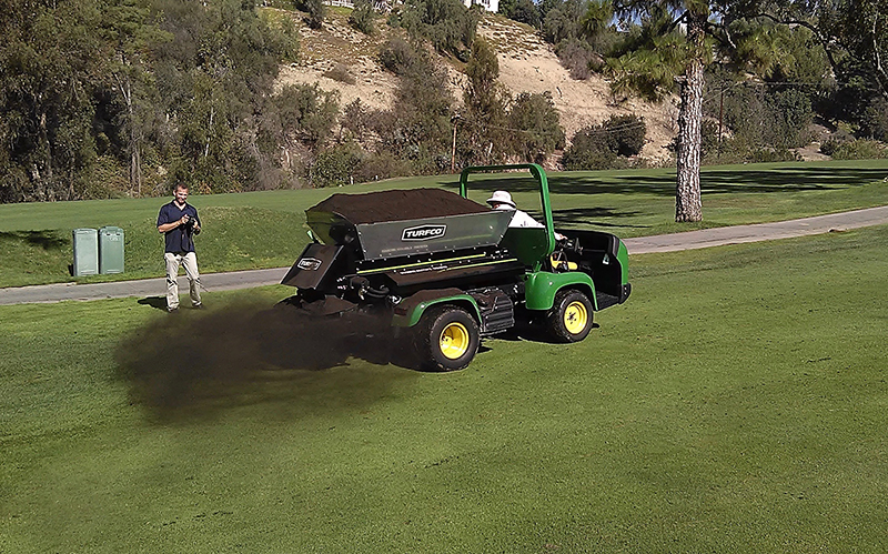 Applying biochar at a golf course to reduce watering needs.
