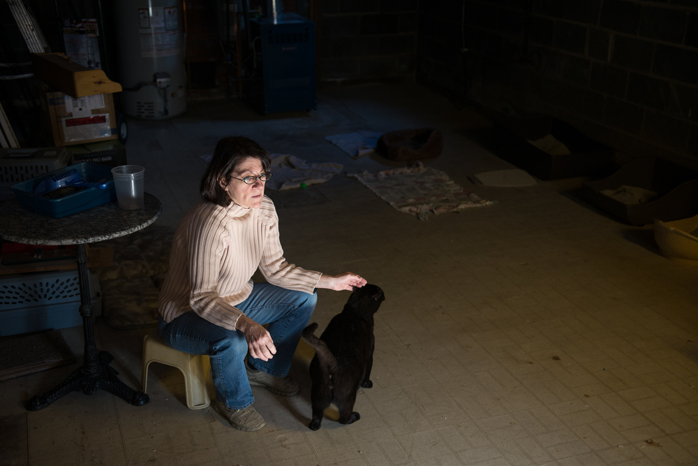 Laurice Ghougasian sits in the basement of her home, where she cares for 11 cats, many of which are former ferals she has rescued.