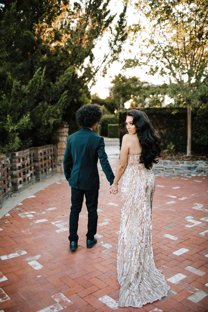 Engagement session with glamorous dress looking over shoulder at estate in Los Angeles