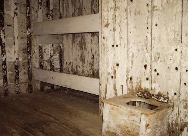 Inside the Old Gaol. Bunks and a toilet.