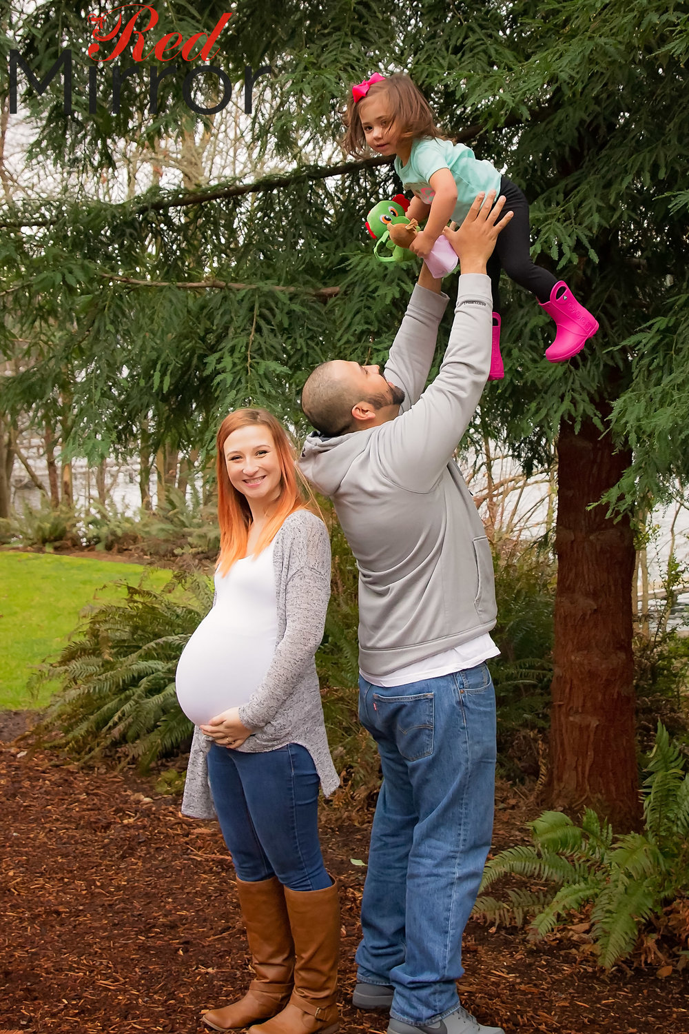 Family image with Dad throwing big sister into the air while Mum cradles her bump