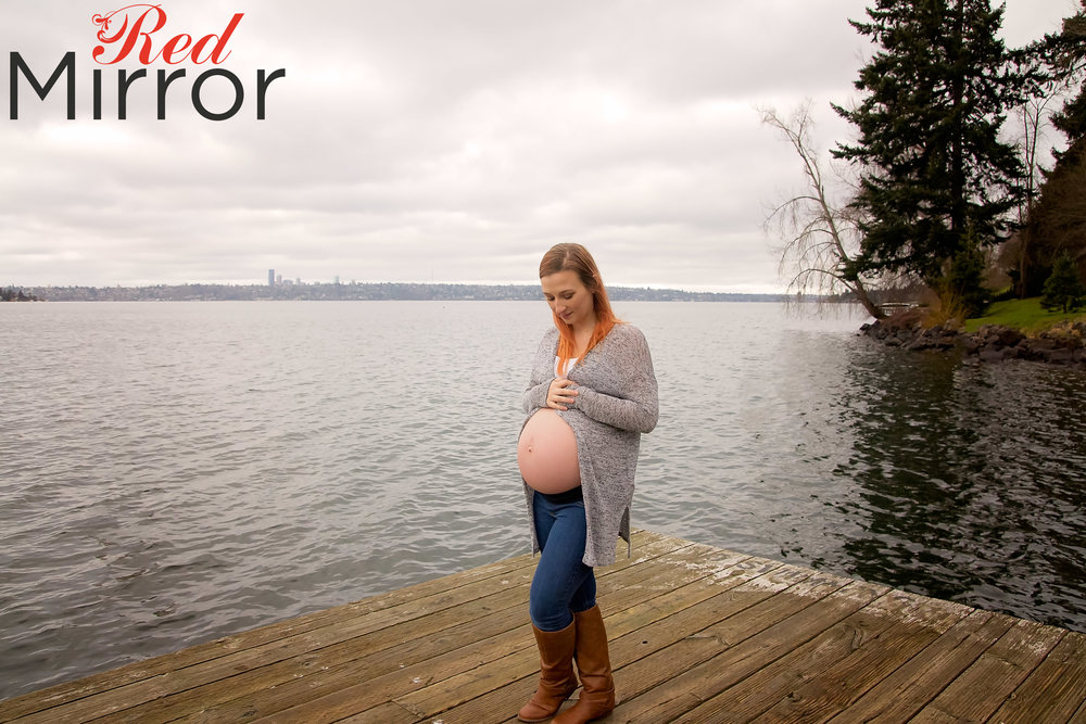 Mum with her exposed bump, looking serene against the lake