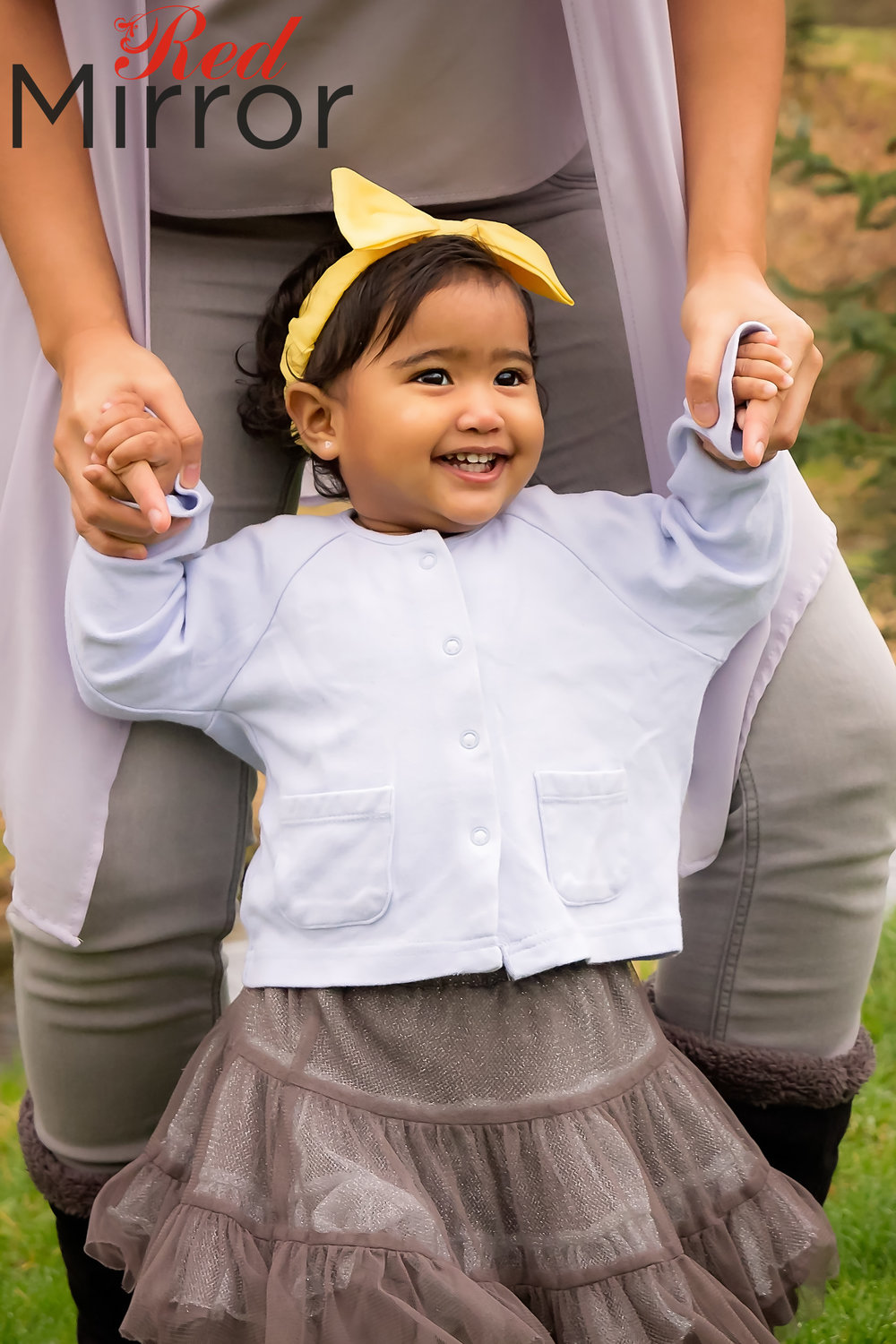 Little girl holding her mothers hands. She is wearing a grey tutu and yellow headband