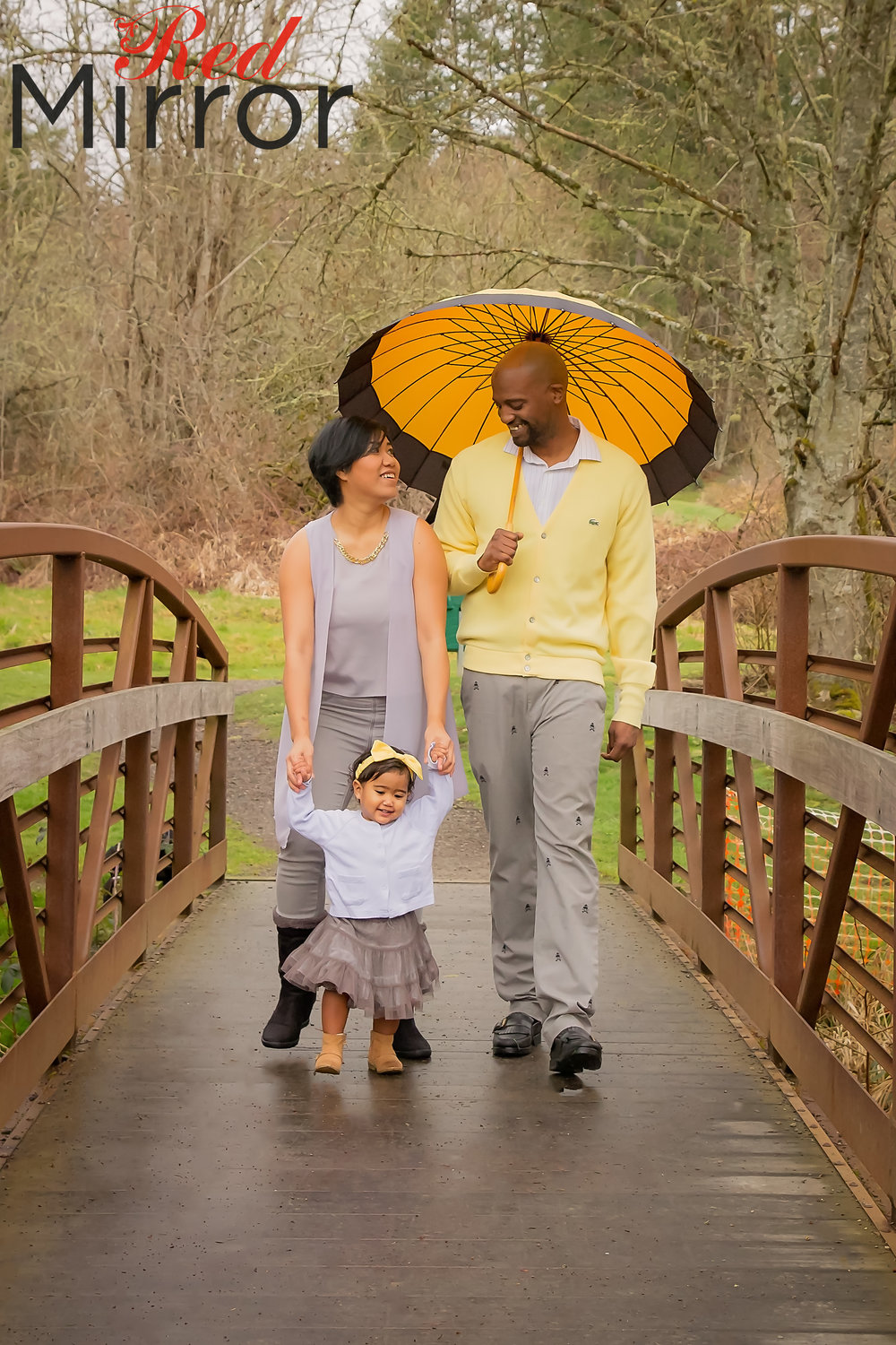 Mother and Father walking along a bridge with a little girl in front of them. The father is carrying a yellow umbrella