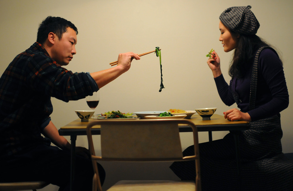 From left, Kai Qiao and his wife Yang Wang eat dinner in their new apartment on Wednesday, March 5, 2014. A couple of the dishes included a spicy beef and celery stir fry and hot and sour shredded potatoes.