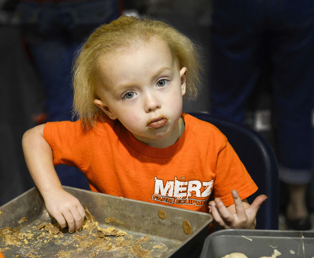 Natalie Witt, 2, finishes off a pan of leftover peanut butter and rice crispies used in making peanut butter bacon balms for the dessert recipe contest. Witt was there with Merz Farm Equipment who came from Fall City, Neb. to participate in the BaconFest.