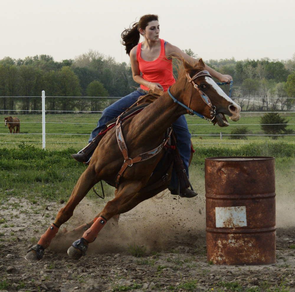 Amee Riley, 19, practices barrel racing with her horses in front of her house on Tuesday, May 6, 2014.