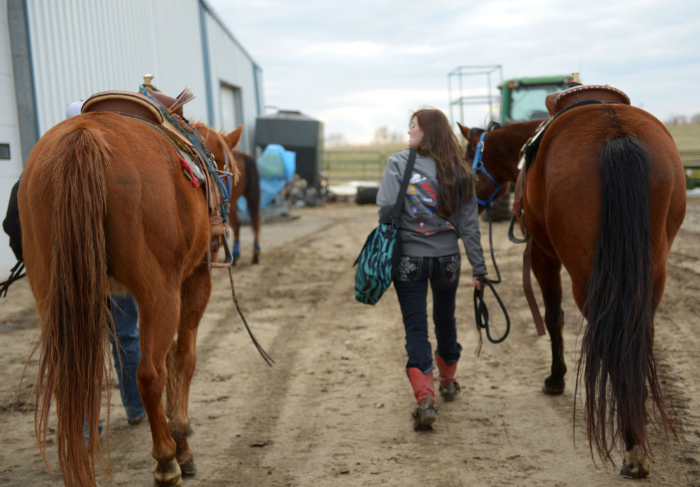 "Amee walks with her horses Banjo and Pistol before a barrel racing competition in Centerview, Mo. To deal with nerves before competing, Amee says she will ""take a deep breath and tell myself, 'It's just a race, there will be more.' I don't need to be all nervous."""