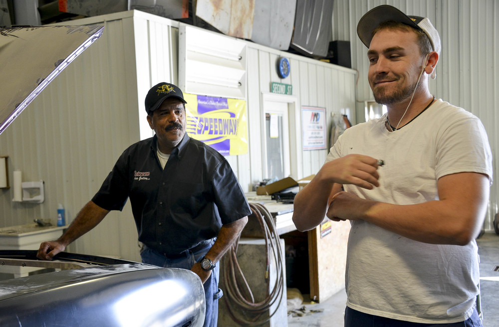 """Howard checks on Teel's progress on a 69' Camaro for a local customer. """"I probably wouldn't change it,"""" Teel said. """"But working with him can get on my nerves just because he's my dad."""""""